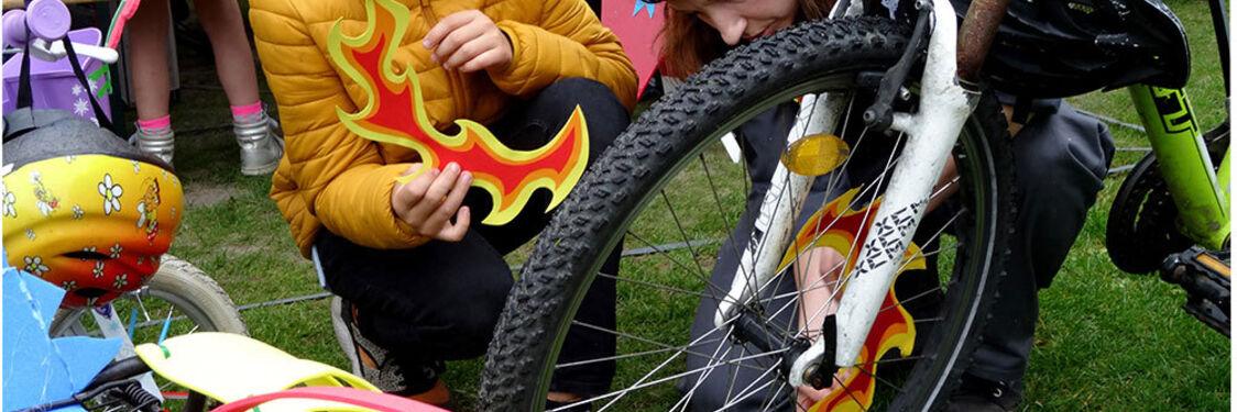 """Reklame for arrangementet """"Hjulestue"""". Billedet forestiller to unge mennesker der reparerer en cykel."""